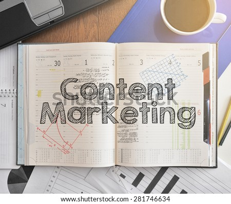 Notebook with text inside Content Marketing on table with coffee, some diagrams on paper and laptop  - stock photo