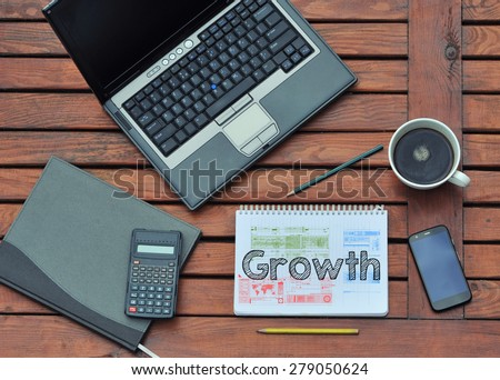 Notebook with text inside Growth on table with coffee, mobile phone  - stock photo