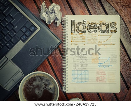 Notebook with text inside Ideas on table with coffee, laptop pc and crumpled sheets
