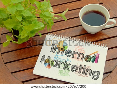 Notebook with text inside Internet Marketing on table with coffee and plant. - stock photo