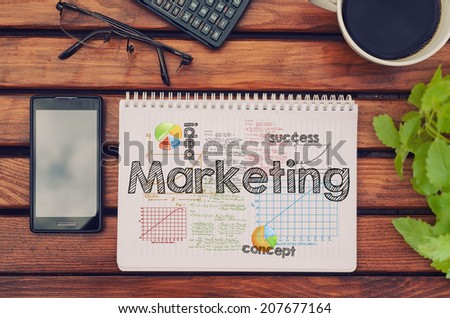 Notebook with text inside Marketing on table with coffee, mobile phone and glasses.  - stock photo