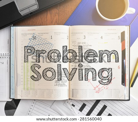 Notebook with text inside Problem Solving on table with coffee, laptop and some sheet of papers with charts and diagrams - stock photo