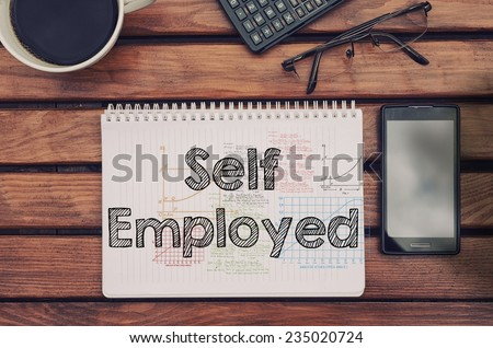 Notebook with text inside Self Employed on table with coffee, mobile phone and glasses.  - stock photo