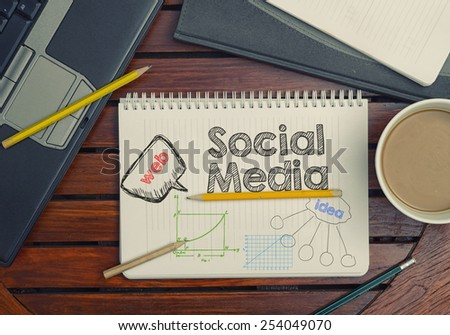 Notebook with text inside Social Media on table with coffee, notebook and pencils  - stock photo