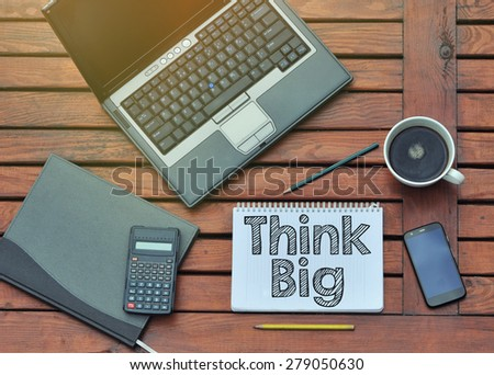 Notebook with text inside Think Big on table with coffee, mobile phone  - stock photo