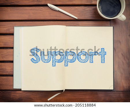 Notebook with text Support inside on table with coffee - stock photo