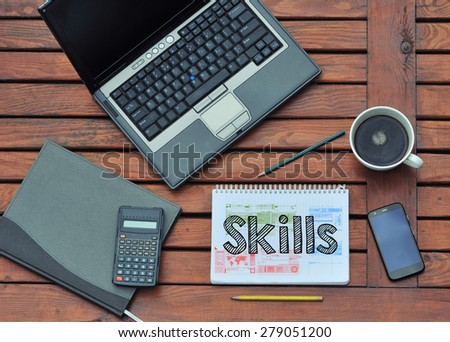 notebook with the note in the center about Skills - stock photo