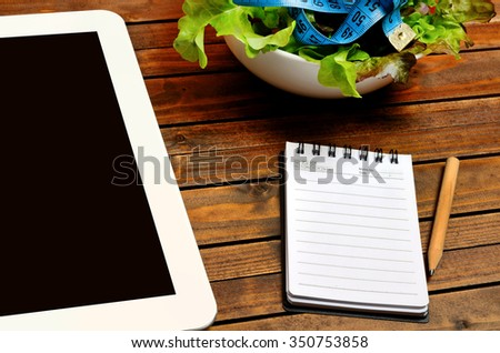 Notebook with vegetable salad and digital tablet on table