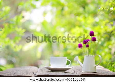 Notebook with white coffee cup and  globe amaranth in mini water pot  at outdoor - stock photo