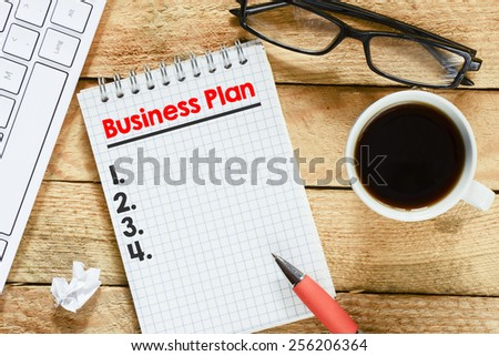 Notebook with with business plan. Workplace with keyboard , coffee , notebook with with business plan list and pen on wood table - stock photo