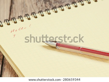 Notebook with yellow pages and a red pen, selective focus - stock photo