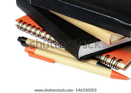 Notebooks and pens isolated on white