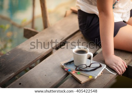 Notebooks, pen, glasses, and coffee cup are putting down on the wood waterside while young woman sitting beside them in morning time on weekend - stock photo