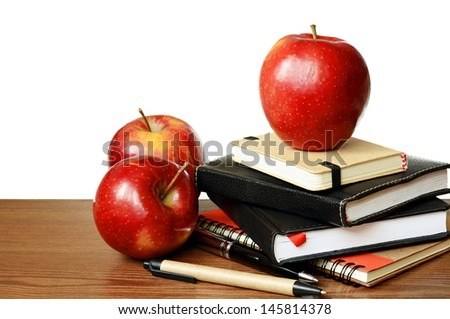 Notebooks, pens and apples on a table isolated on white - stock photo