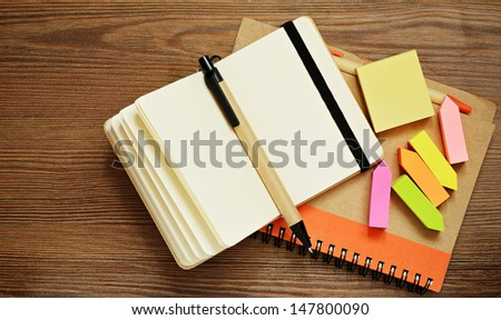 Notebooks, pens, and stickers on wooden background - stock photo