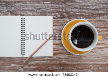 Notepad and coffee cup on wood table. View from above
