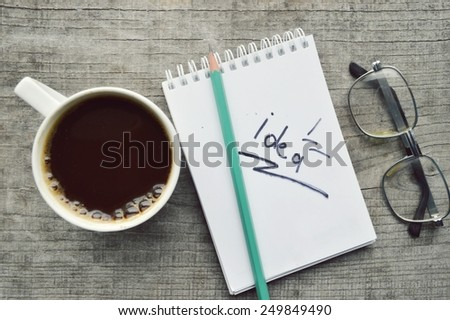 Notepad and Cup of coffee on wooden background. - stock photo