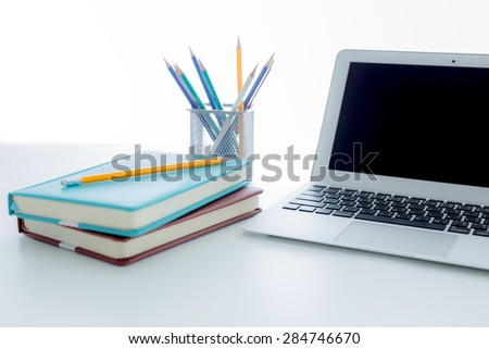Notepad and laptop on wood table.