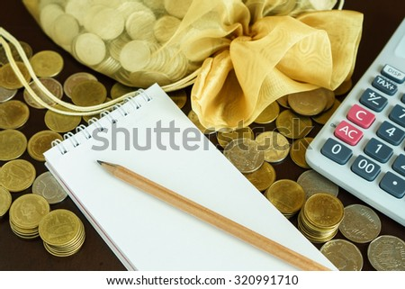 Notepad and money coins on the table, Saving for your investment