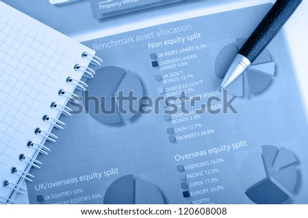 notepad and pen over annual report - stock photo