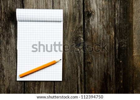 notepad and pencil on a wooden planks - stock photo