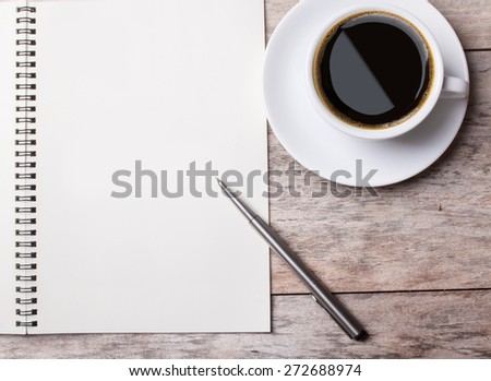 notepad ans a cup of coffee on a wooden desktop - stock photo
