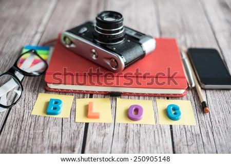 Notepad, camera and smartphone - stock photo