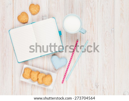 Notepad, cup of milk, heart shaped cookies and gift toy on white wooden table - stock photo