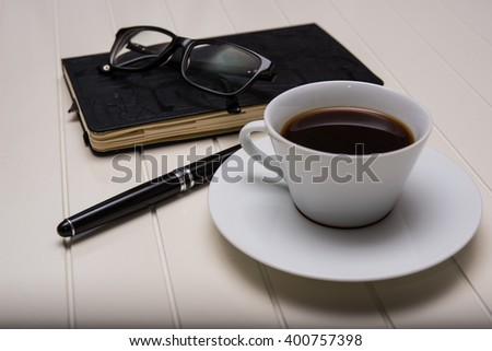 Notepad - daily planner with leather cover and handle black vintage with black glasses and a cup of coffee on white table