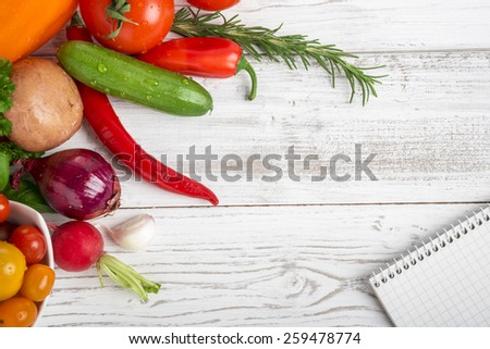 Notepad, fresh vegetables and herbs on wood
