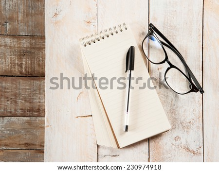 notepad,glasses and ink pen on the wooden - stock photo