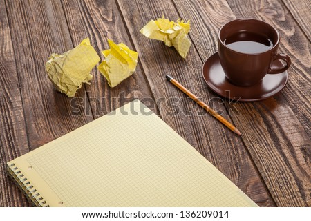 Notepad on a wooden table with crumpled sheets around - stock photo