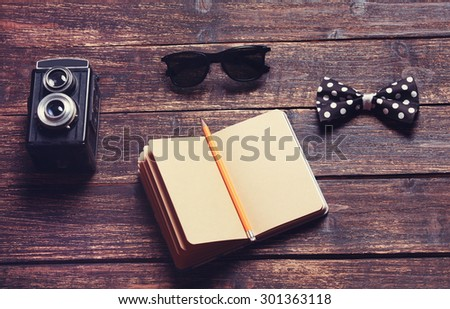 Notepad on a wooden table  with old camera and acsessorize  - stock photo