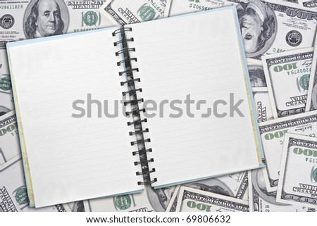 notepad on dollars background - stock photo