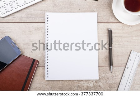 Notepad, pen, tea and smartphone on wooden table - stock photo