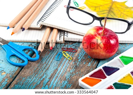 Notepad, pencils, scissors, paper clips and glasses. Office or school supplies on wooden planks painted in blue.