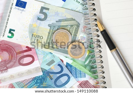 Notepad with a pen on the background of Euro banknotes.