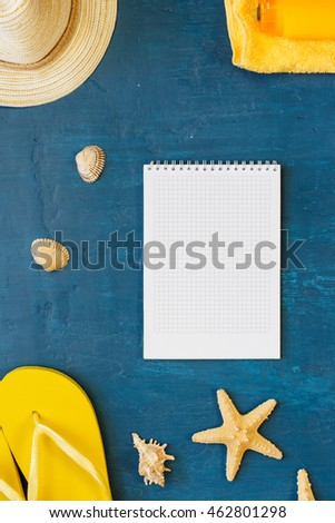Notepad with blank page with different beach accessories on blue surface, top view