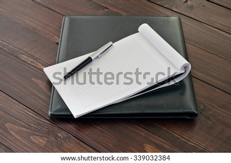 Notepad with blank pages with a pen on the leather business folder on the office table close up. Top view. Copy space - stock photo