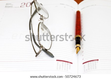Notepad with eyeglasses and pen
