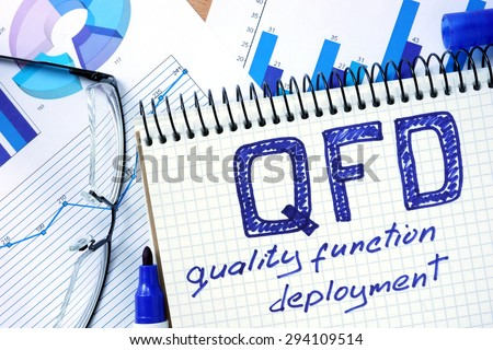 Notepad with inventory QFD - Quality Function Deployment on office wooden table. - stock photo
