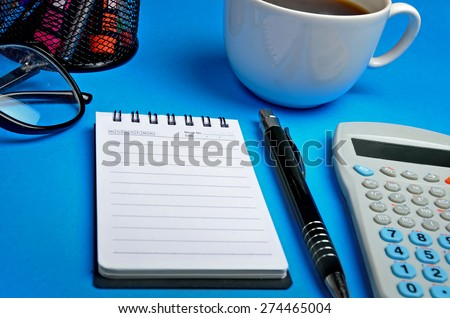 Notepad with office supplies on blue background - stock photo