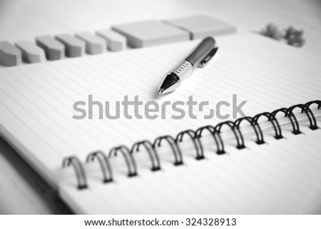 notepad with office supplies on white table black and white tone color style