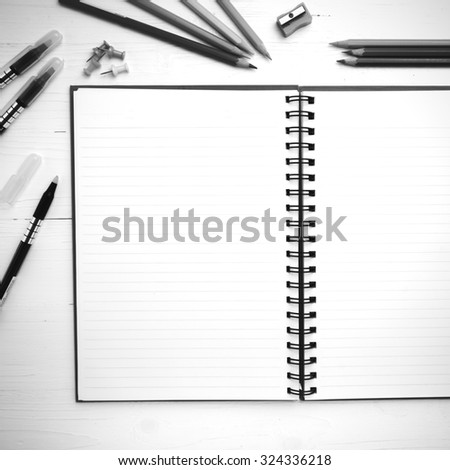 notepad with office supplies on white table view from above black and white tone color style