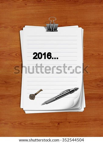 "Notepad with paper clip isolated on a wooden surface. A pen and an old key are on the paper. ""2016"" is written on the notepad as a reminder."