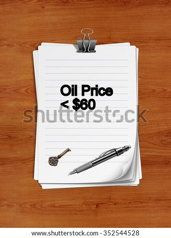"Notepad with paper clip isolated on a wooden surface. A pen and an old key are on the paper. ""Oil Price < $60"" is written on the notepad as a reminder."
