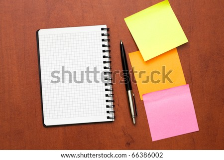 notepad with pen and reminder notes lying on the table