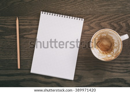 notepad with pencil on wood table and empty coffee cup, vintage toned