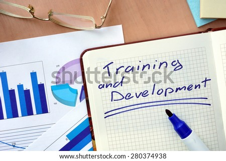 Notepad with words training and development  concept and marker. - stock photo