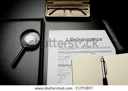 Notepads, glasses and life insurance papers - stock photo